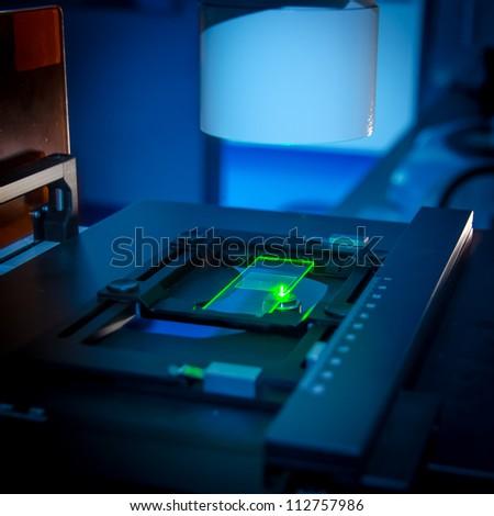 science slide under fluorescent microscope - stock photo
