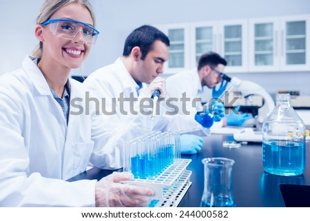 Science student using pipette in the lab to fill test tubes at the university - stock photo