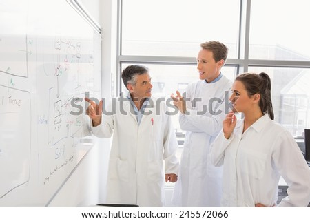 Science students and lecturer looking at whiteboard at the laboratory - stock photo