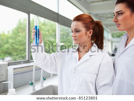 Science students looking at a graduated cylinder in a laboratory