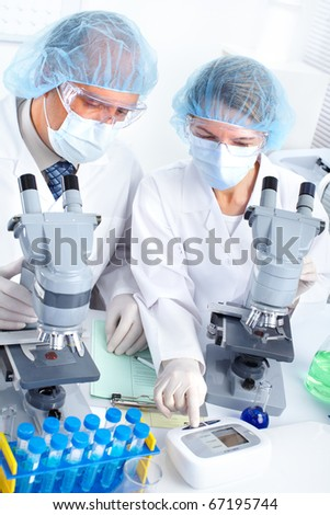 Science team working with microscopes in a laboratory - stock photo