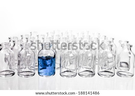 Science Vials in Rows with one vial filled with a light blue liquid. - stock photo