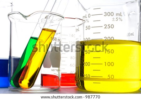 Scientific beakers filled with colored liquid. - stock photo