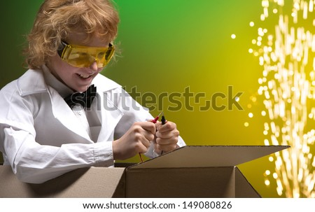 Scientific experiment. Cheerful little boy sitting a the cardboard box and testing wires while isolated on coloured background - stock photo