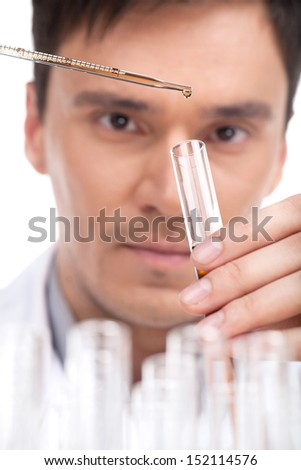 Scientific experiment. Close-up of confident young man making scientific experiment