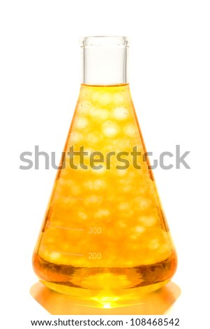 Scientific laboratory glass conical Erlenmeyer flask with yellow floating chemical liquid molecular suspension for a chemistry experiment in a science research lab - stock photo