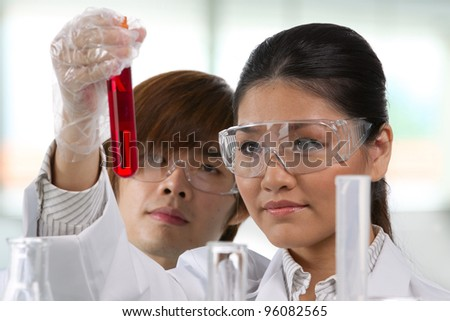 Scientific researchers looking at a liquid solution. - stock photo