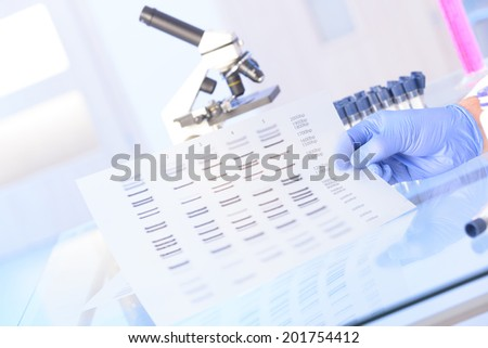 Scientist analizing DNA sequence for identity - stock photo