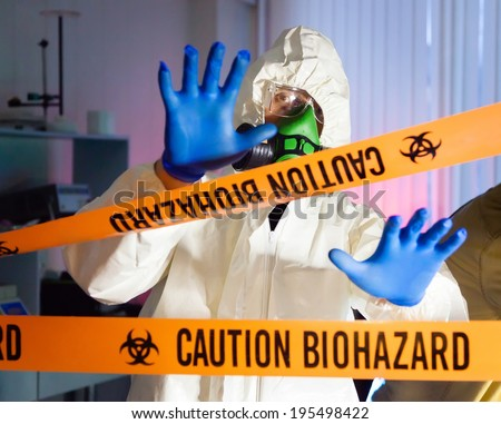 Scientist behind caution tape in hazardous biochemicals laboratory. - stock photo