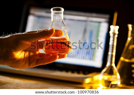 scientist doing research and holding a beaker - stock photo