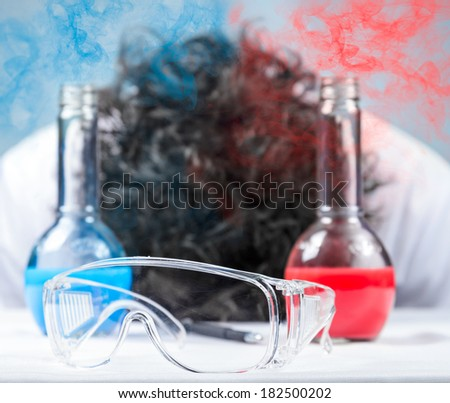 Scientist Dr. unconscious. In the foreground of the tube. Focus on glasses - stock photo