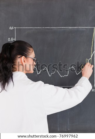 Scientist drawing charts on the blackboard in a lab - stock photo