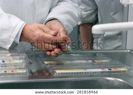 Scientist hands holding syringe performing microbiological strain identification test in laboratory. - stock photo