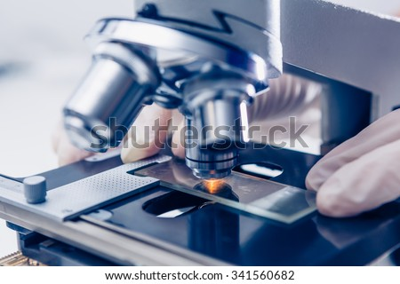 Scientist hands with microscope close-up shot in the laboratory - stock photo