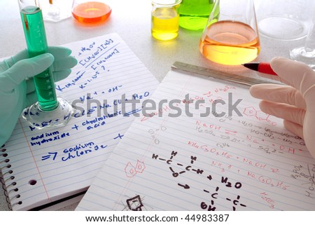 Scientist holding a pen over chemistry formulas notepads for assay notes comparison and laboratory technician handling a scientific cylinder with green liquid for experiment in a science research lab - stock photo