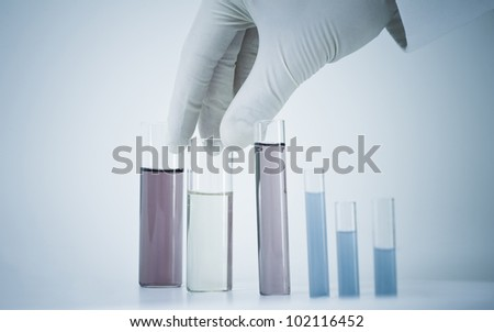 Scientist holding test tube in blue monochrome. - stock photo