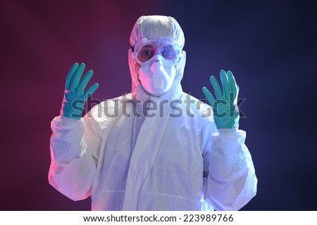 Scientist in full protective hazmat suit with dramatic lighting as background - stock photo