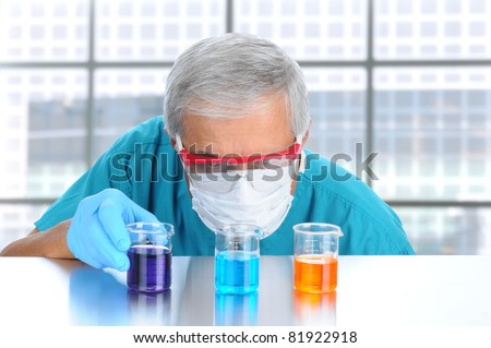 Scientist in modern laboratory with protective mask and goggles examining laboratory beakers filled with different chemicals. Horizontal format.