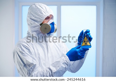 Scientist in protective overall, respirator and gloves holding flask with biohazard fluid in lab - stock photo
