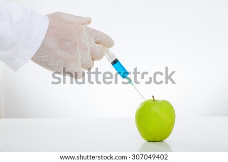 Scientist injecting chemicals into an apple. Close up on hand. - stock photo