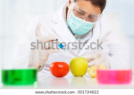 Scientist injecting chemicals into an apple, tomato and corn - stock photo