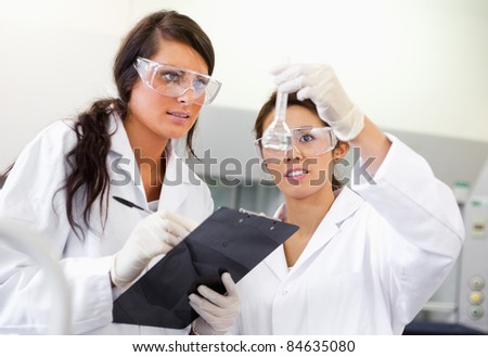 Scientist looking at a Erlenmeyer flask in a laboratory - stock photo