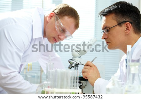 Scientist looking at specimen while his assistant helping him
