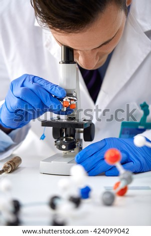 Scientist looking through a microscope in a laboratory - stock photo