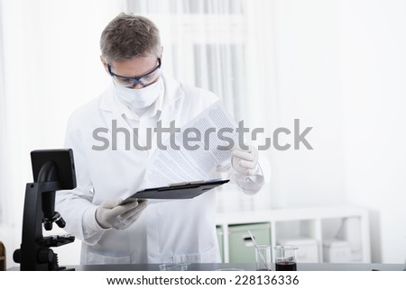 scientist or doctor working with clipboard, microscope and blood, in lab or hospital - stock photo