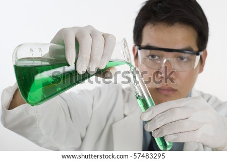 Scientist pouring chemicals in a laboratory - stock photo