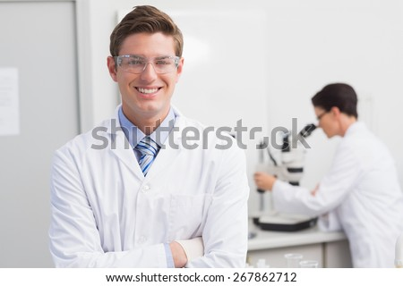 Scientist smiling at camera arms crossed and another working with microscope in laboratory - stock photo