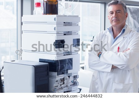 Scientist standing with arms crossed next to the machine in laboratory - stock photo