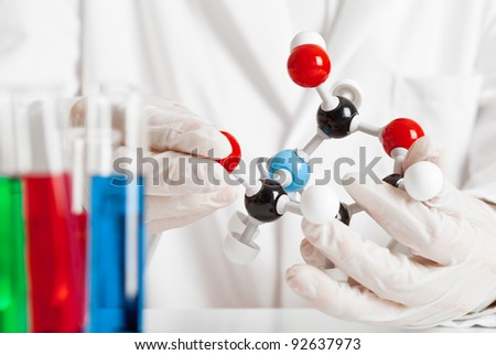 Scientist studying molecule model with test tubes in the foreground