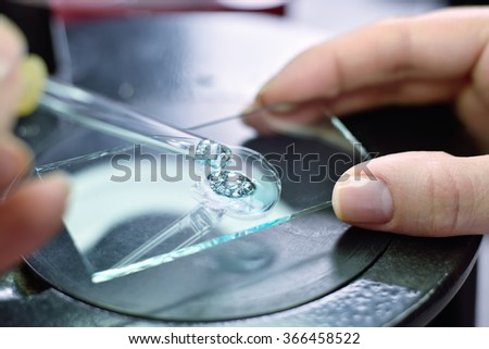 Scientist taking a sample of blue liquid with a pipette - stock photo