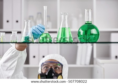 Scientist taking flask with green liquid from the shelf