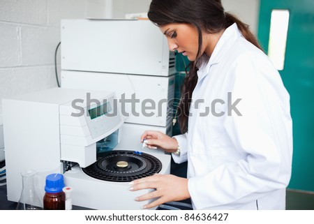 Scientist using a centrifuge in a laboratory - stock photo