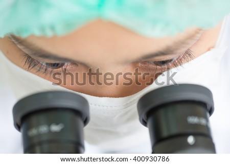 Scientist using a microscope in a laboratory  - stock photo