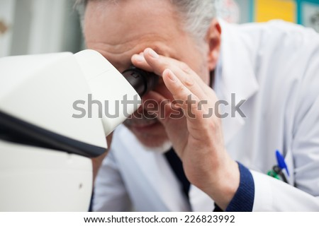 Scientist using a microscope in his laboratory - stock photo