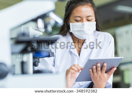 Scientist using tablet in laboratory - stock photo