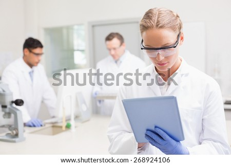 Scientist using tablet while colleagues working behind in laboratory - stock photo