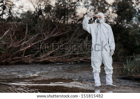 Scientist wearing a chemical protection suit takes a sample of contaminated water.  On a background of nature. - stock photo