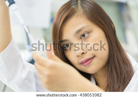 Scientist with pipette and test tube, examining samples and liquid in laboratory - stock photo