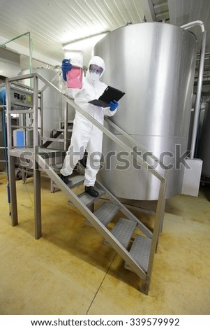 scientist with tablet checking sample in industrial interior
