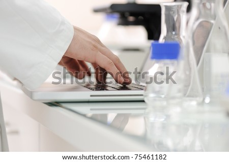 Scientist working at lab with laptop, microscope and tubes - stock photo
