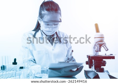 scientist writing report with equipment and science experiments with lighting effect vintage style - stock photo