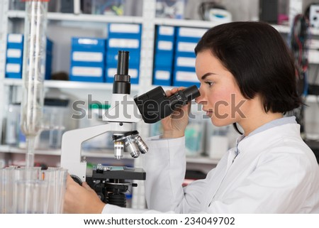 Scientist young woman using a microscope in a science laboratory