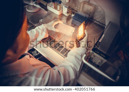 Scientists are testing the use of light LED to kill cancer cells in the lab. Vintage - stock photo