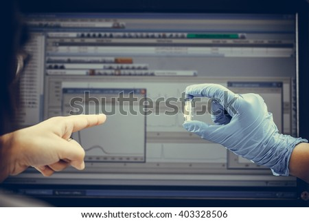 Scientists look at computer graphs of experimental results in lab Vintage - stock photo