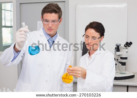 Scientists looking attentively at beakers in laboratory - stock photo