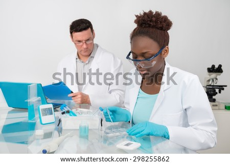 Scientists, male and female, work in research facility. Mature scientist supervises work of younger colleague. Focus on the eyelashes of female  student - stock photo